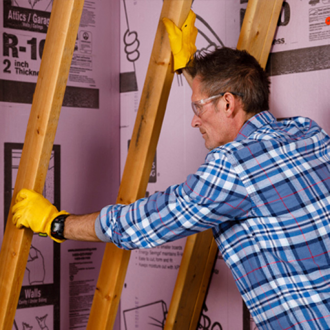 man installing Foamular in a basement