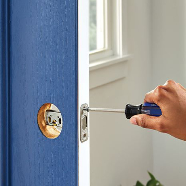 Person using screwdriver to install the deadbolt throw of the Schlage keypad lever on front door.