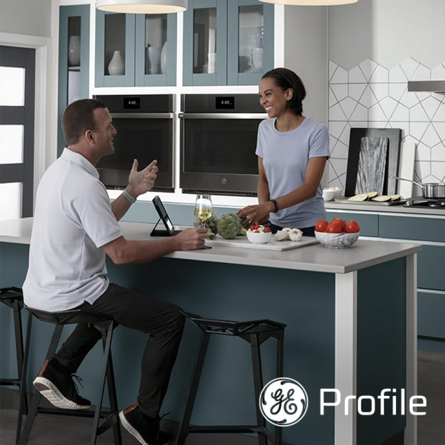 A couple laughs as they talk in a modern kitchen.