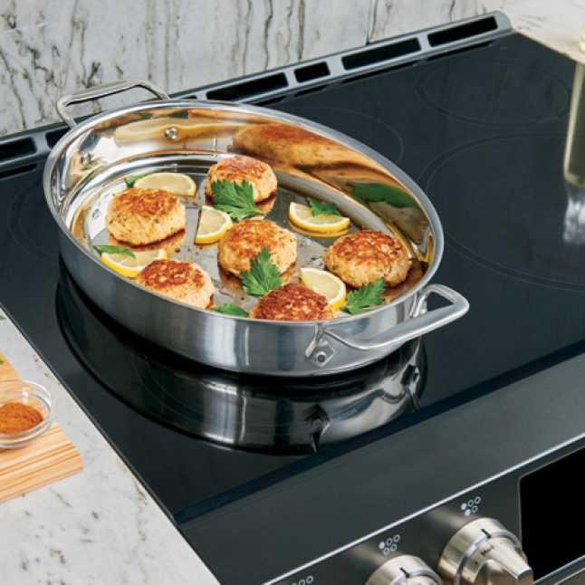 A large oval pan sears food and seasonings on top of two combined burners.