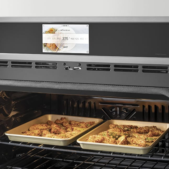 Two trays of food are fried to a crispy golden brown in the oven.