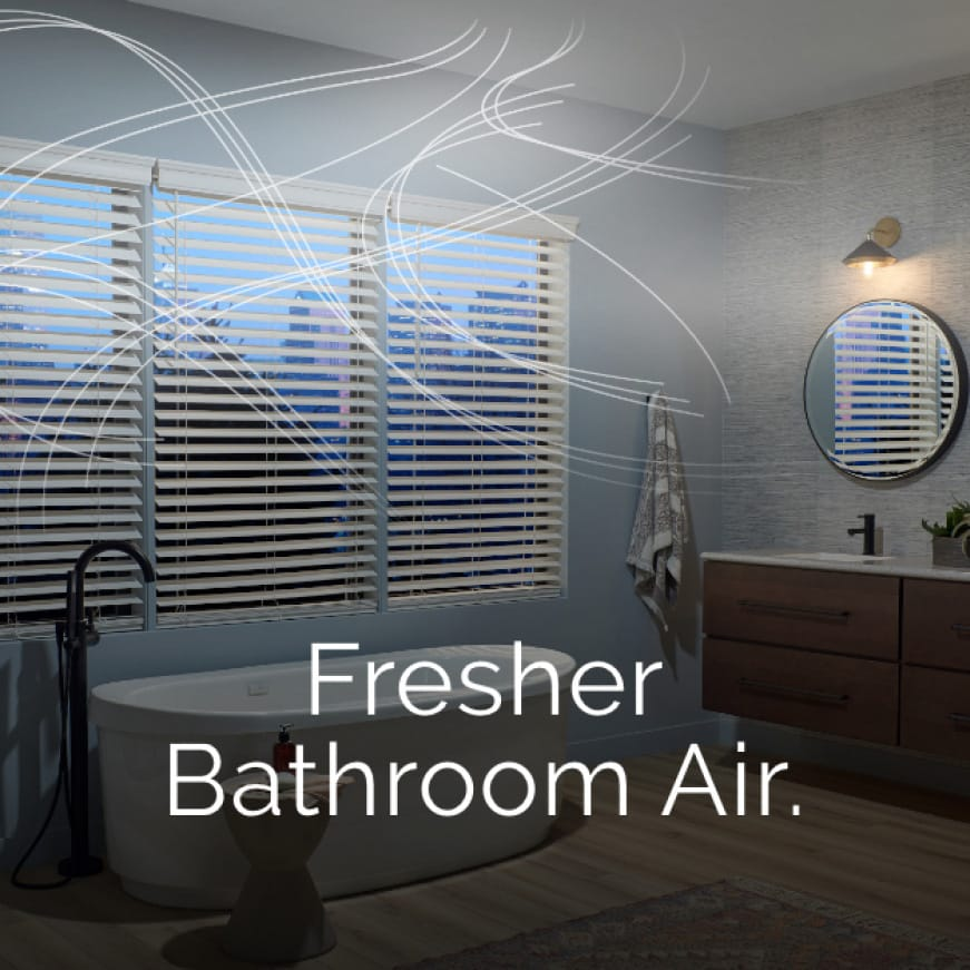 Image of a modern bathroom with a tub in front of a window that overlooks a cityscape. Wispy lines circle around the room to represent air movement.