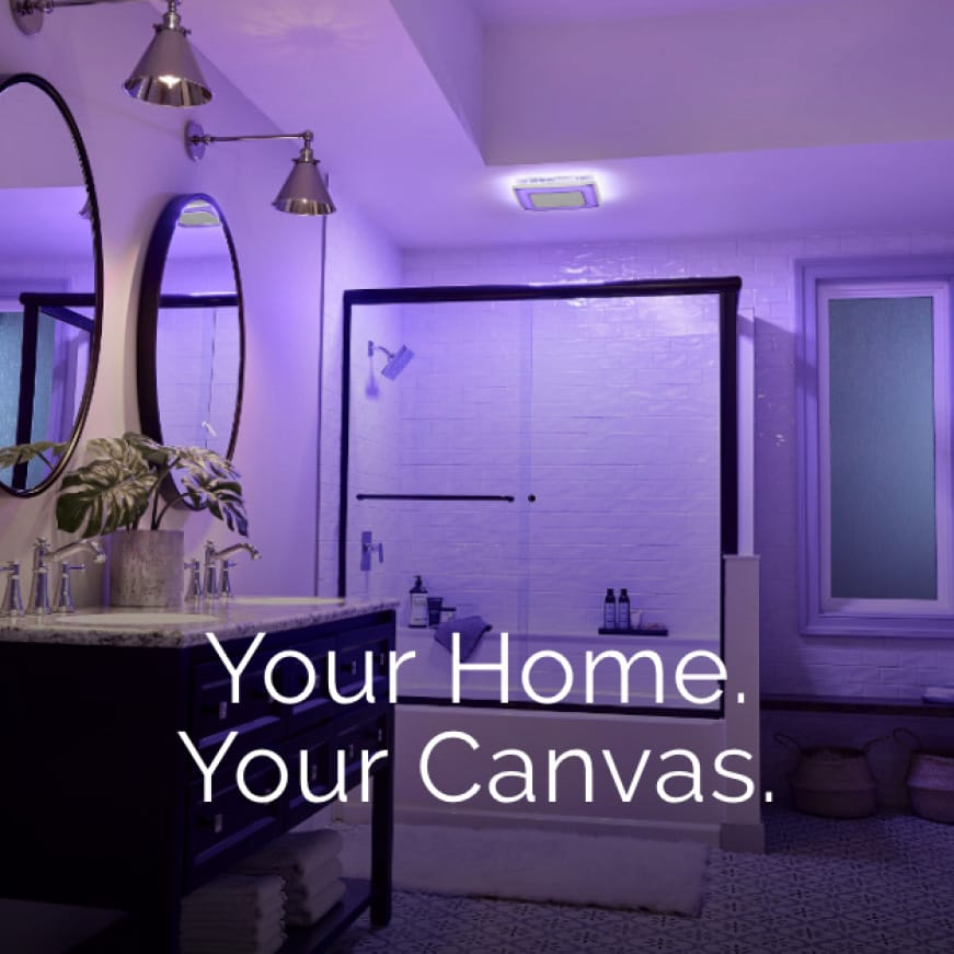 Image of a modern bathroom with a ChromaComfort fan  over the shower illuminating a violet color. Words on top say: Your Home. Your Canvas.