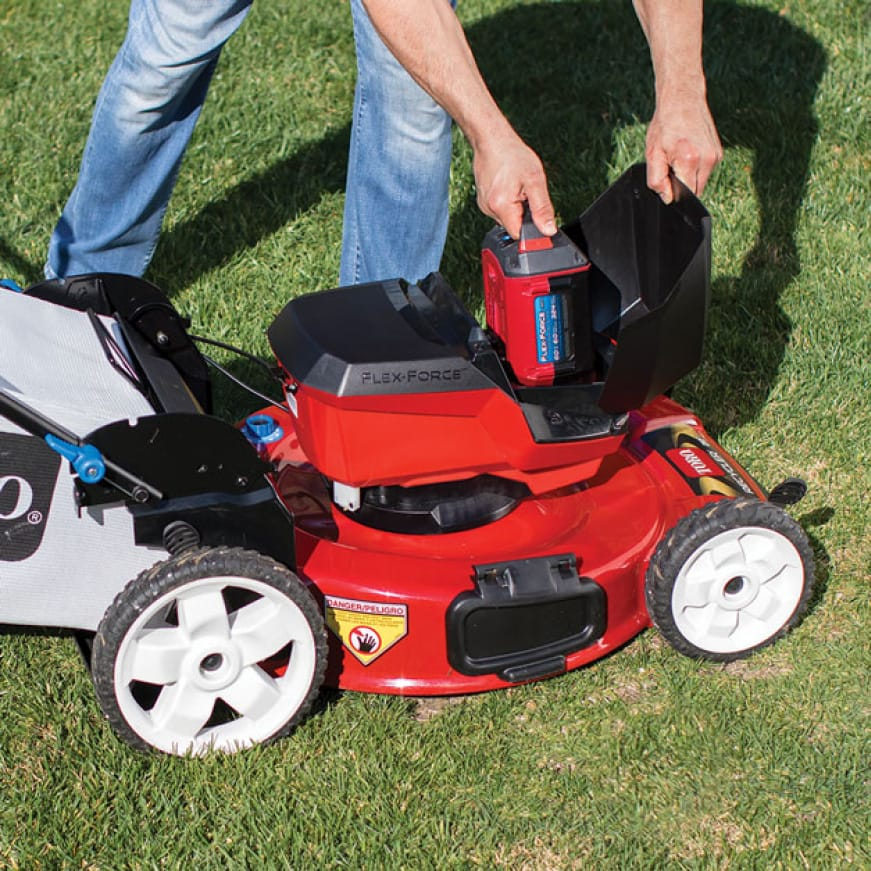 person easily putitng a battery into the mower