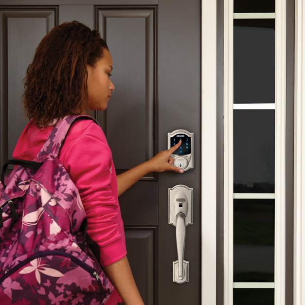 Girl with backpack using the Schlage Connect Smart Deadbolt touchscreen.