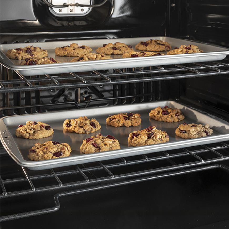 Two trays of cookies bake evenly inside the oven's cavity.