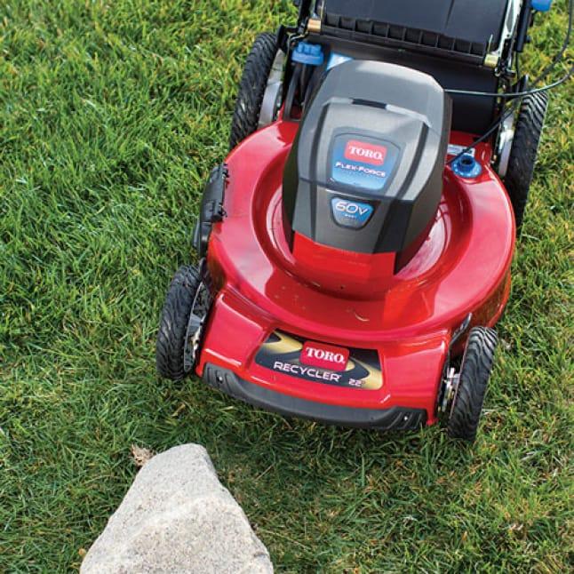 close up on Toro's durable steel deck lawn mower near a rock