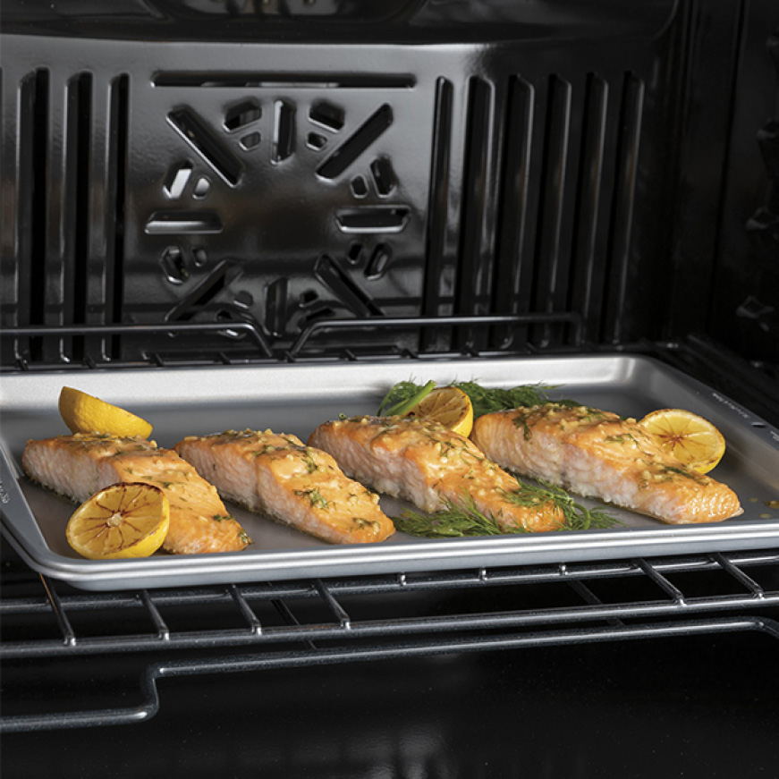Fish and citrus cook inside the oven as the fans circulate hot air.