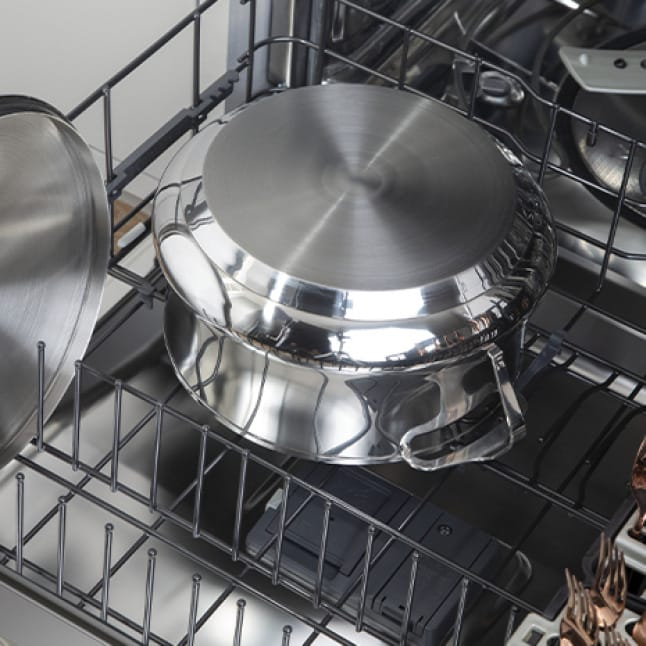 A pot has been placed into the lower rack of the dishwasher along with copper utensils and other cookware.