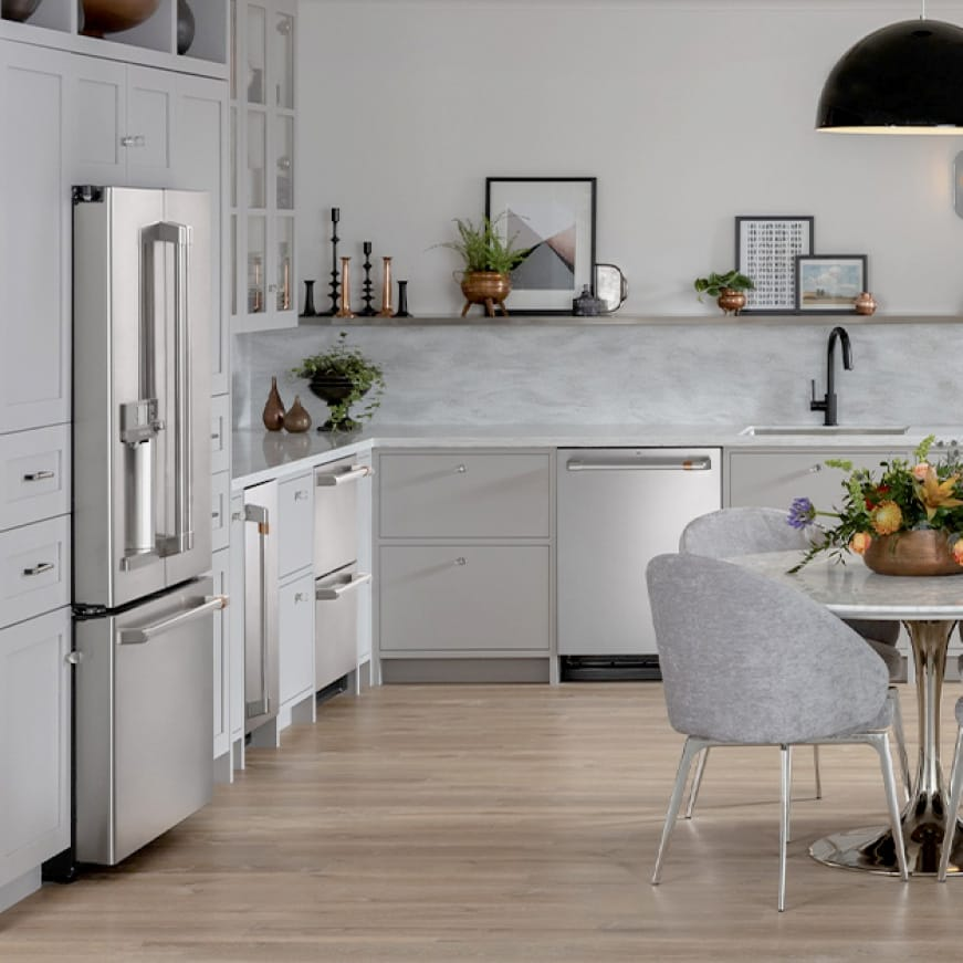 Light pours in through a window into a modern gray kitchen equipped with stainless Cafe appliances. A pot sits on the range's glass cooktop.
