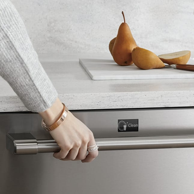 A woman grabs the dishwasher handle.