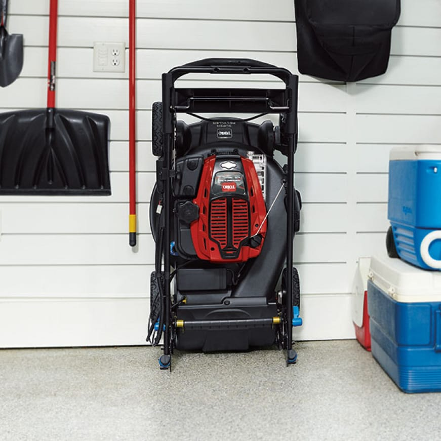 person in their garage with their mower folded up against the wall taking up minimal space.