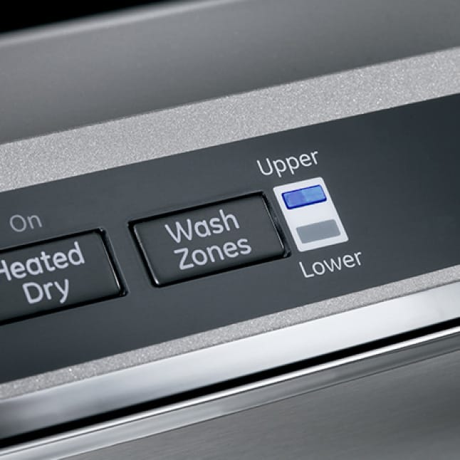 A close-up of the dishwasher's hidden top panel. An indicator light next to the wash zone button shows that an upper half-wash is currently running.