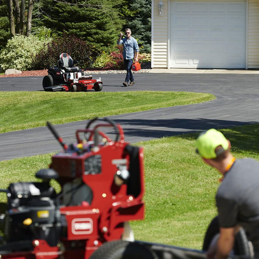 image of professional landscape contractor with their Toro professional mower and the happy homeowner with their Toro zero turn mower