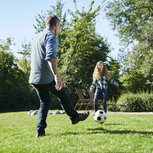 father and daughter playing soccer in the yard