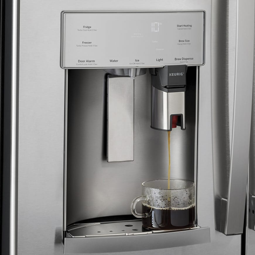 The keurig nozzle built into the external dispenser drips coffee into a clear mug.