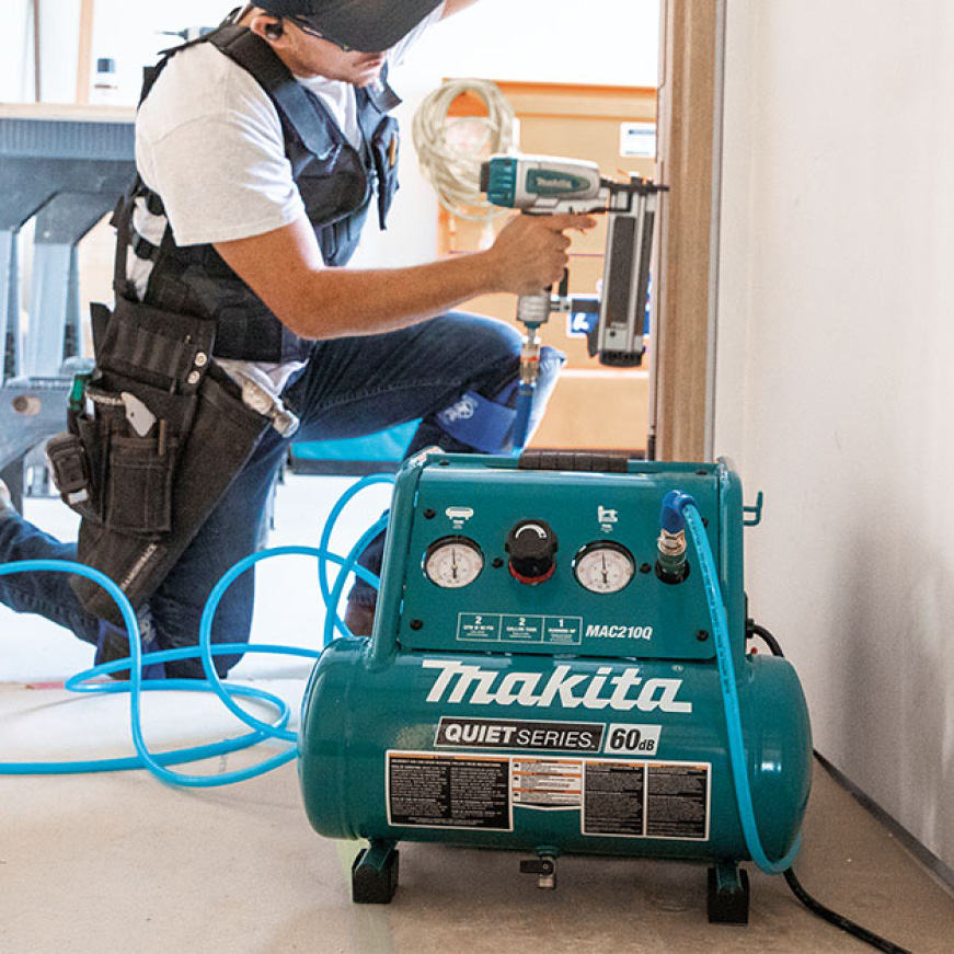 A professional using Makita air compressor to power his Makita nailer