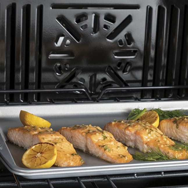 Fish bakes on a sheet inside the oven. The fan and vents of the oven are clearly visible.