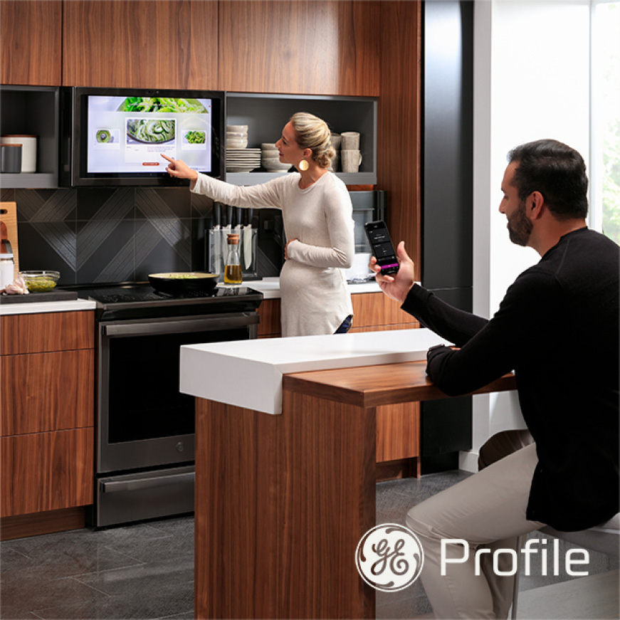 Woman and man in kitchen interacting with the range and Kitchen Hub