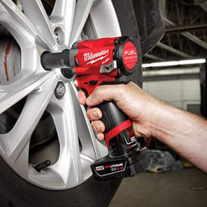 A man removing lug nuts from a car tire with the M12 FUEL Stubby Impact Wrench.