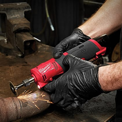 """Metal Fabricator wearing gloves uses the M12 FUEL 1/4"""" Straight Die Grinder to cut a pipe."""