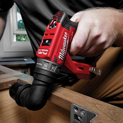 A man uses the M12 FUEL Installation Drill/Driver to install cabinetry.