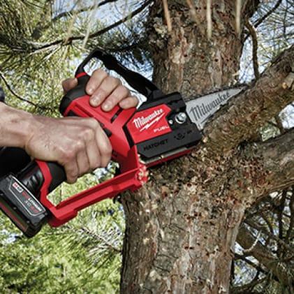 Man using M12 FUEL Hatchet to cut tree branch
