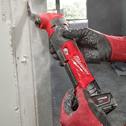 A man wearing work gloves uses the M12 FUEL Oscillating Multi-Tool to cut through drywall.