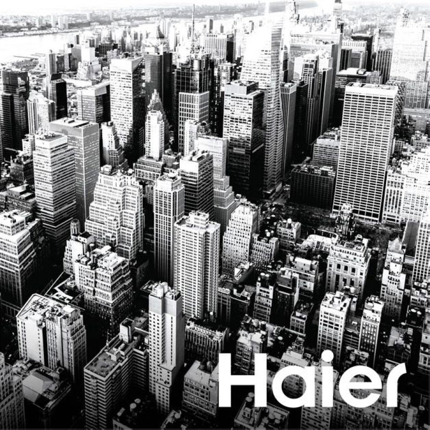 A black and white photo showing a birds-eye view of a city. The Haier logo is superimposed over the center of the photo.