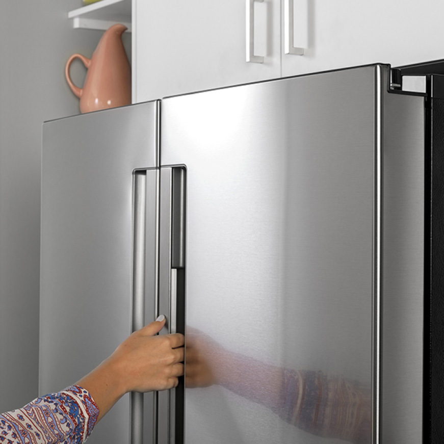 A hand grabs the recessed handle of the refrigerator door to open it.