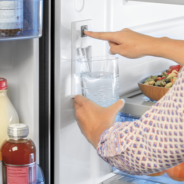 A person holds a glass of water to the internal dispenser. As a finger presses the button, water pours into the glass.