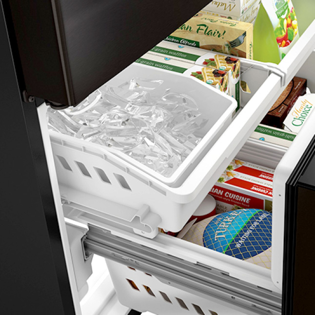 A close-up of the icemaker, installed in the upper left corner of the freezer drawer.