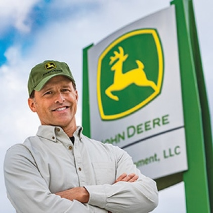 Image showing a John Deere dealer in front of a John Deere dealership sign