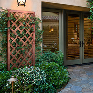 A lifestyle shot showing the trellis along an exteroir wall with ivy growing