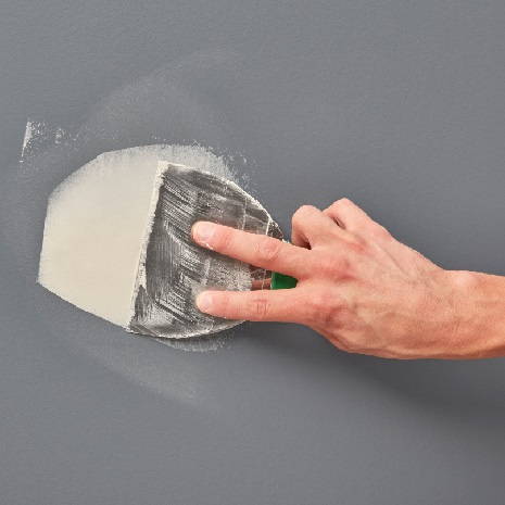 Close up of hand using taping knife and joint compound to repair hole in wall
