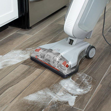 Up close view of the Hoover Professional Series FloorMate Deluxe Hard Floor Cleaner cleaing a kitchen floor.