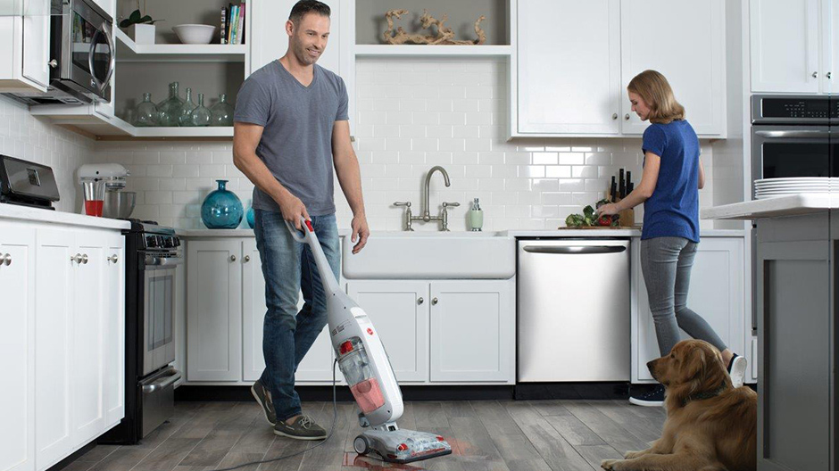 The Hoover Professional Series FloorMate Deluxe Hard Floor Cleaner being used in a kitchen by a man with a woman and dog near by.