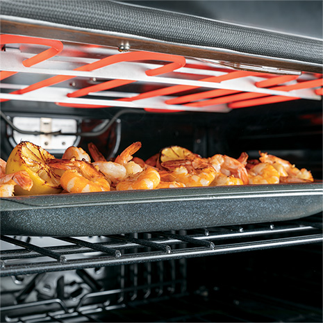 Image of shrimp and lemons on a pan under broil element inside the oven