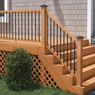 A side veiw of a stair railing featuring the rectangular balusters leading to a backyard