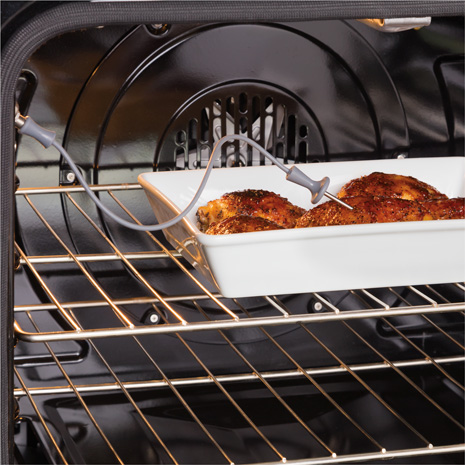 Cooked chicken in a dish in the oven with probe inserted in the meat