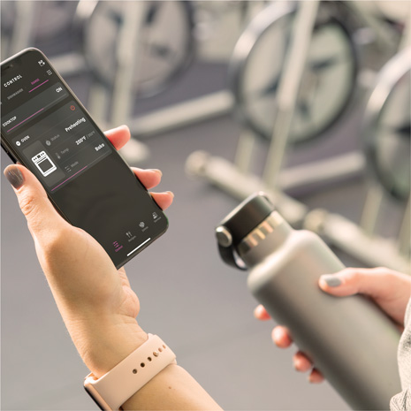 Woman holding an iPhone in a gym with SmartHQ app screen showing the oven preheating remotely