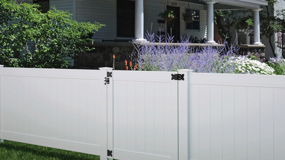 A view of the 4 ft woodbridge fence panel with a gate dividing two properties in an urban setting.