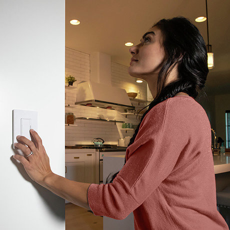 Person using a dimmer to adjust multiple lights in the room