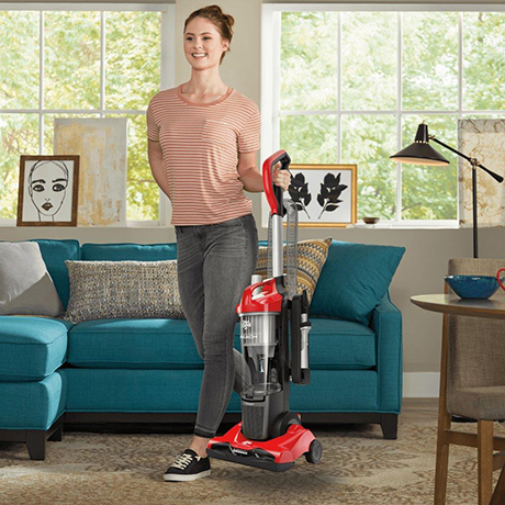 A college student carrying the Dirt Devil Endura Reach Upright Vacuum Cleaner showing its lightweight and compact design.