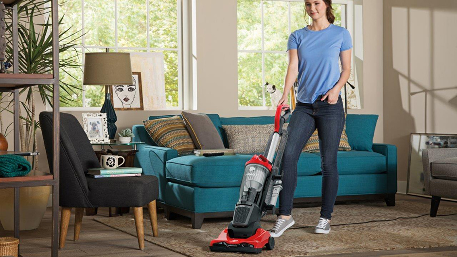 A college student using the Dirt Devil Endura Reach Upright Vacuum to clean their living room.