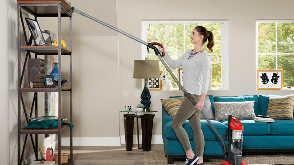 A college student using the Dirt Devil Endura Reach Upright Vacuum Cleaner quick release want to clean the top of a shelving unit.