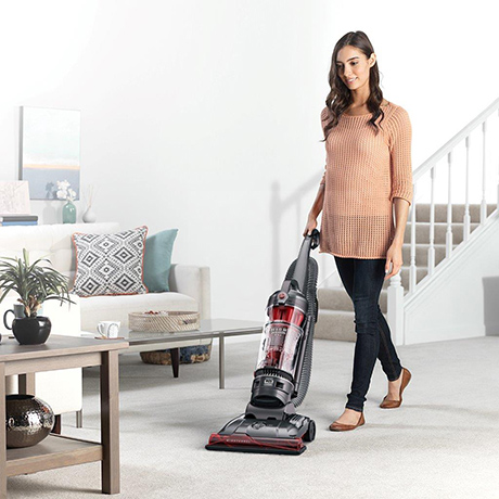 A woman using the Hoover WindTunnel 3 Max Performance Pet Upright Vacuum cleaner in a living room on carpet.