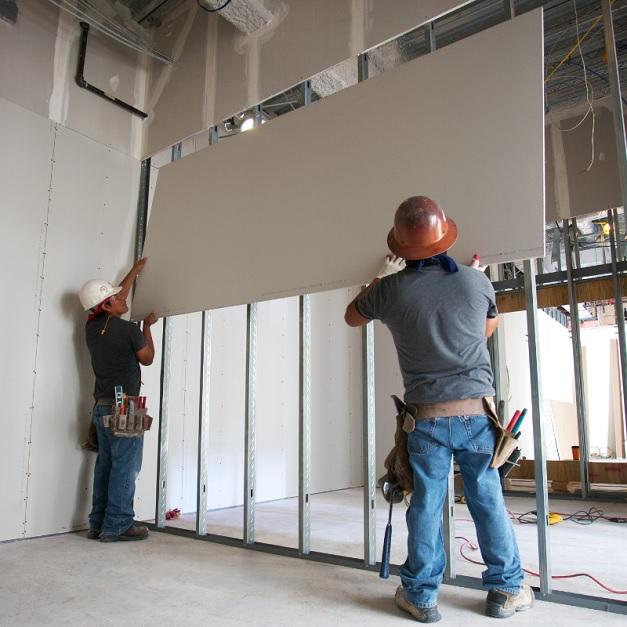 Two men installing wallboard on steel beams