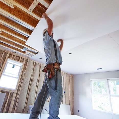Man lifting wallboard overhead to apply on ceiling