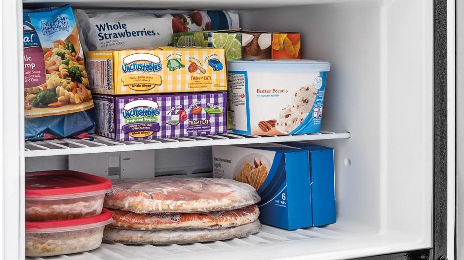 Frozen food on wire freezer shelf.